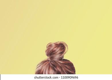 Вид на затылок женщины. Волосы завернутые в булочку на светло-желтом пастельном фоне. Концепция завершения содержания.