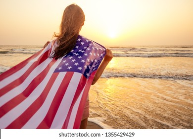 view from the back young brunette female person holding national American flag cover ocean beach holiday travel at summer romantic sunset .America independence day concept