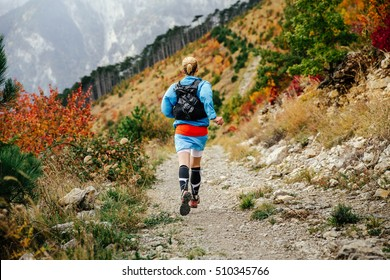view back young female runner runs mountain trail  in autumn forest. compression socks in feet