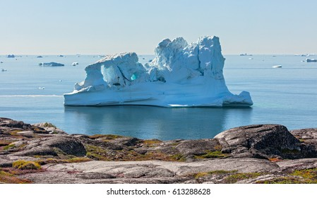 The view in the backlight of a very big iceberg in Disco Bay, Greenland. View from Oqaatsut village. This is a consequence of the phenomenon of global warming and catastrophic thawing of ice