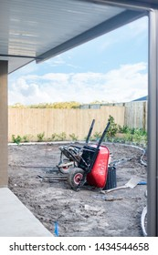 A view of the backyard of the house with machinery and saplings planted alng the fence.