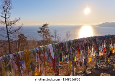 View of Baikal Lake from a popular viewing platform on the rock of Chersky stone with colorful ribbons and Buddhist prayer flags on the railing of a gazebo at sunset