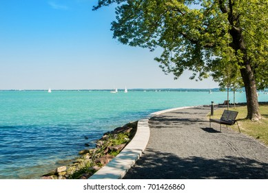 A view of Balaton lake with white yachts at the horizon and trees, bench and footpath at the foreground, Tihany, Hungary.