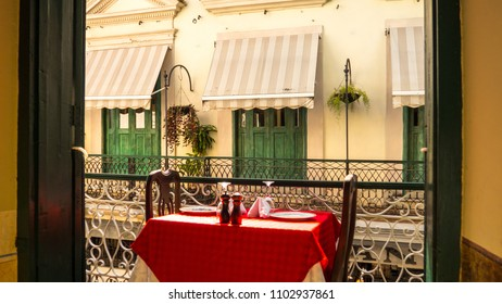 View from balcony to another balcony, romantic situation with table for two and beautiful view of old street, Havana, Cuba