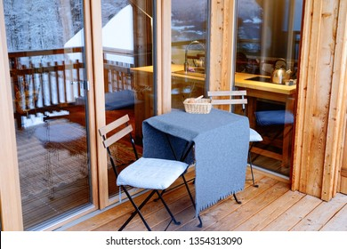 View from Balcony of living room on Austrian Alps mountains reflected in glass windows in snow winter. Design of modern apartment house with open terrace. Table with chairs