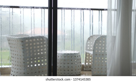 View of the balcony with table and chairs in the pouring rain with windy.