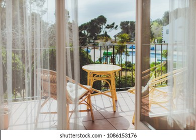 View from balcony with wicker table and wicker chairs to sea, pool with water and trees. Summer vacation in a warm country. SPAIN