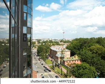 View from balcony window of modern building. Summer sunny day. City landscape. Reflection at the glass wall
