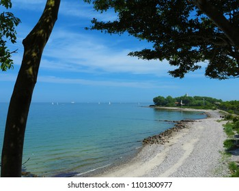 view to the baltic sea coast with beach and boats surrounded by a tree