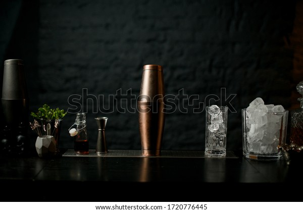 view of bar counter on which stands copper shaker and glasses with ice and other miscellaneous bar equipment