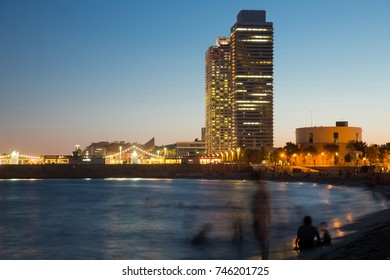 View of Barceloneta beach with Mapfre tower and Arts Hotel in Barcelona in sunset