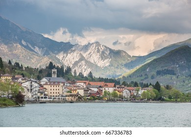 view of the Barcis city on the lakeside surrounding mountains against a dramatic cloudy blue sky background in Valcellina, Pordenone, Italy