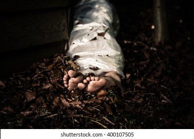 View of the bare feet of the wrapped body of a homicide victim lying in leafy detritus in the darkness in a conceptual image of violence and crime