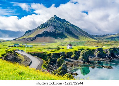View of the basalt rocks formation on the coastline with the beautiful houses and the Mountain Stapafell in the background at Arnarstapi Village in summer sunny day in Iceland