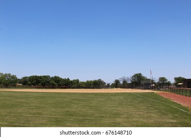A view of a baseball diamond from behind the fence in left field.