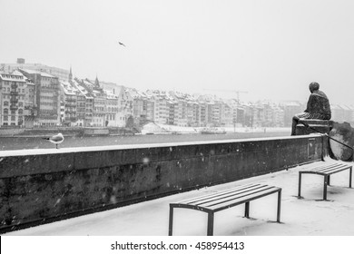 View Of Basel City Houses Near River In Cold, Snow Covered Winter Setting With Statue, Seagull And 2 Benches On Other Side In Vintage Black And White
