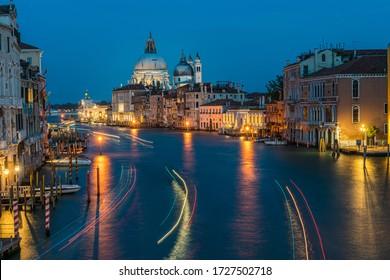 View of Basilica di Santa Maria della Salute and grand canal from Accademia Bridge at night in Venice, Italy.