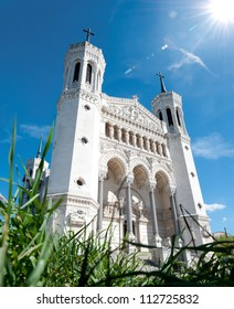 View of Basilica of Notre Dame de Fourvi���¨re (Fourviere) on a sunny day. Green grass in foreground and blue sky with sun and clouds in background. Lyon, France, Europe.