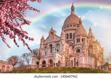 View of Basilica Sacre Coeur in Montmartre in Paris, France. Spring time with cherry blossom tree and rainbow on the sky.