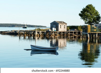 View of Bass Harbor Maine from the deck of Thurston's Lobster pound with a dock, lobster traps, boat house, tree and row boat reflections visible. A fishing boat is in the background,