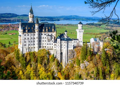 View of the Bavarian Neuschwanstein Castle, which is located on the top of the mountain from above. Bavarian valley in autumn. View of the German castle on the mountain in autumn.