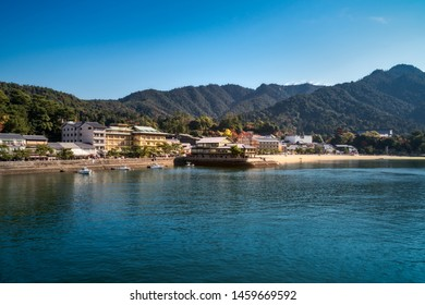 View from the bay of the coast of Miyajima Island in autumn with Itsukushima Shrine and Mount Misen in the background - Hiroshima Bay, Japan.