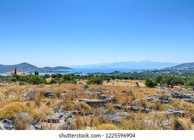 A view of the bay at Elounda from a hillside. Rocks and scrubland are in the foreground leading to some buildings, the sea and distant hills.