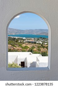 A view of the bay at Elounda through a window.  Open country and buildings lead to the sea and hills are in the distance.