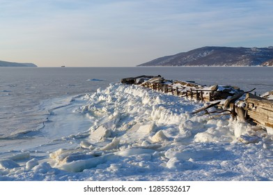 View of the bay Nagaeva and an old abandoned pier. Far away on the horizon can be seen the ship and the mountains. The sea is covered with ice. Broken mooring structures. Magadan, Far East of Russia.