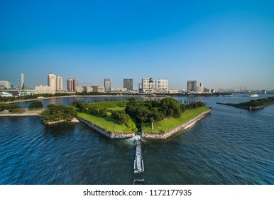 View of the bay of Odaiba with daiba park and the beach in the distance.