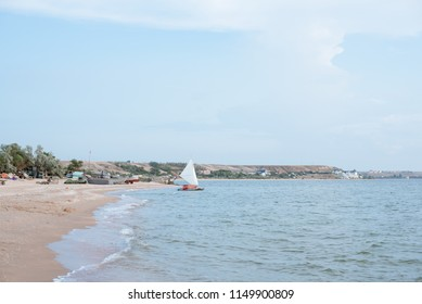 View of the bay, sandy beach and sail. Horizontal photo. No people.