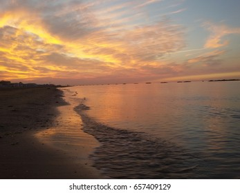 View of a beach of the Adriatic coast in Italy under the light of a beautiful sunset over the sea