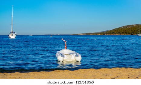 View of a beach with an inflatable boat and in the background the wild coast in Palau (Sardinia, Italy), marine reserve of the Maddalena Archipelago.