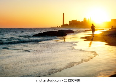 View of beach and lighthouse Maspalomas at sunset.  Gran Canaria.