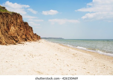 View to a beach near the city. Golden sand, sea cliff, blue sky with white clouds. Sunny weather. Copy-space. Outdoor shot