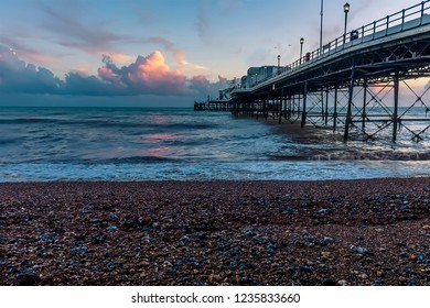 A view from the beach out down the side of the pier at Worthing, Sussex just before sunset