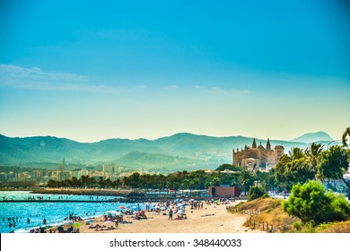 View of the beach of Palma de Mallorca with people lying on sand and the gorgeous cathedral building visible in background. Palma-de-Mallorca, Balearic islands, Spain.