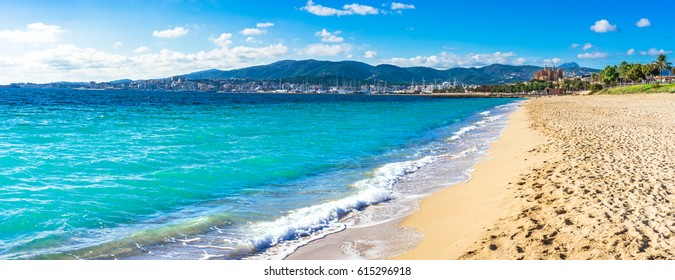 View of the beach in Palma de Mallorca with the town and harbor in background, beautiful coastline scenery Spain Mediterranean Sea, Balearic Islands.