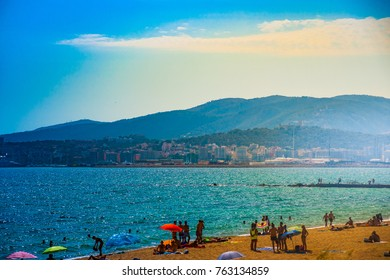 View of the beach of Palma de Mallorca with people lying on sand, aea and palm trees. Palma-de-Mallorca, Balearic islands, Spain.