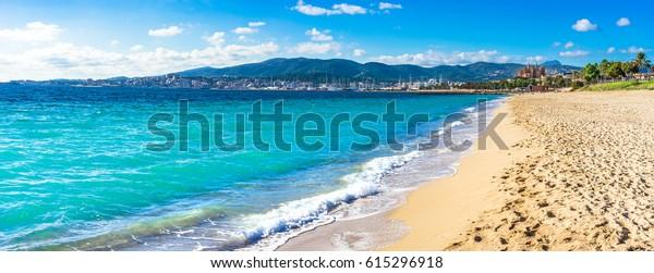 Blick auf den Strand in Palma de Mallorca mit der Stadt und Hafen im Hintergrund, schöne Küstenlandschaft Spanien Mittelmeer, Balearen.