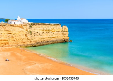 View of beach with rock cliffs and white church in Armacao de Pera town , Algarve, Portugal