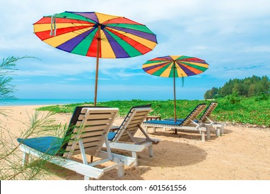 View at the beach sitting behind three yellow chairs a tables and two sunshades