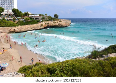 View of the beach with tourists on the sand in the bay of Cala Domingos between the rocks in the Mediterranean Sea in Spain on the island of Mallorca. Resort town Calas de Mallorca