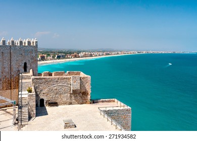 View of the beach at Valencia and the castle of Peniscola. Spain. Beautiful coastline with beaches, hotels and turquoise sea. Part of the old fortress. Clear sunny day, cloudless sky.