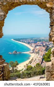 View of beach and village Blanes through a stone arch of the St. John Castle. Costa Brava , Span