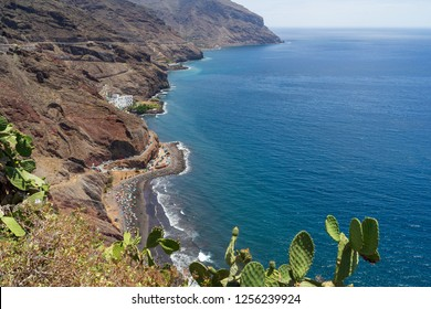 View of the beach with volcanic black sand - Playa de Las Gaviotas and the rocky shore from the observation deck Mirador Las Teresitas. Tenerife. Canary Islands. Spain.