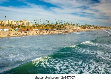 View of the beach and waves in the Pacific Ocean from the pier in Oceanside, California.