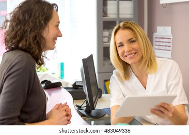 View of a Beautician woman show prices to a customer on a tablet
