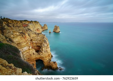 View of the beautiful Algarve coastline from the rocks nearby Lagos, Portugal in unusually cloudy weather. Golden Hour shot.