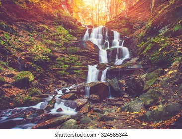 View of a beautiful autumn waterfall in mountains. Filtered image:cross processed vintage effect.